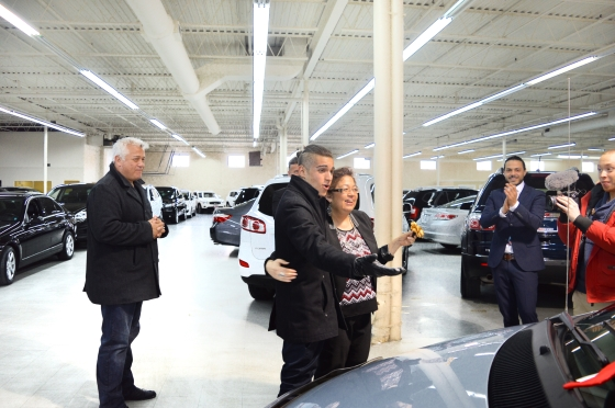 happy son embraces mother after getting free car from autorama
