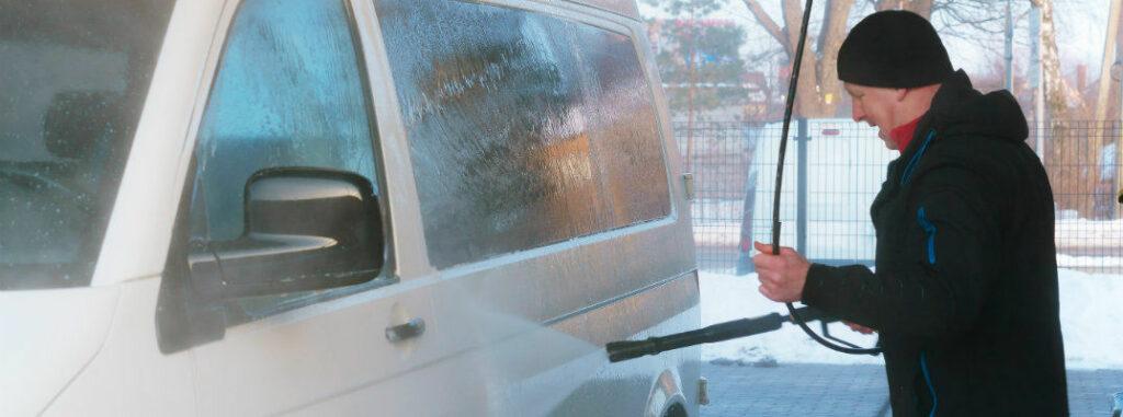 man pressure washing van in winter